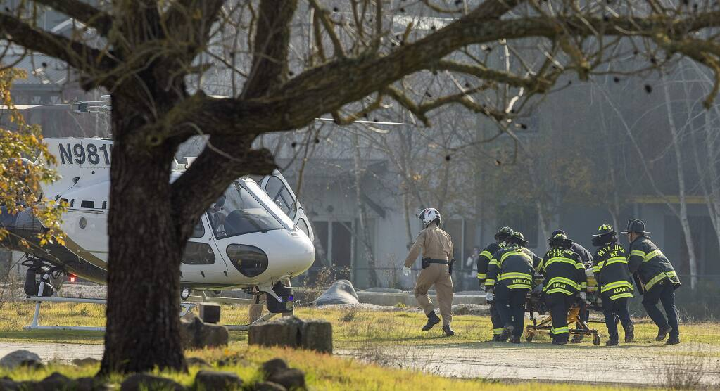 Petaluma firefighter rush a man suffering life-threatening injuries to a helicopter in the Lind Marine facility on the Petaluma River. The worker was trapped under metal casing that collapsed on him while using a cutting torch atop an old silo on Friday, Jan. 3, 2020. (John Burgess/The Press Democrat)