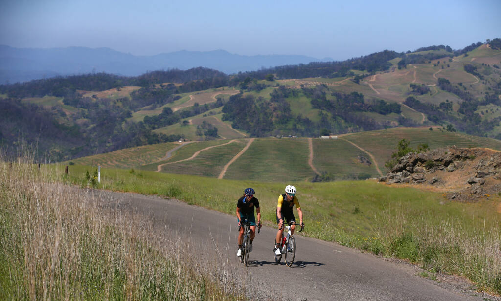 Laura and Ted King ride up Pine Flat Road near Healdsburg on Wednesday, April 21, 2021. The road is one of their favorites because of the scenery, lack of traffic and proximity to Healdsburg. Ted King was a professional cyclist in Europe for 10 years, and was a rider in the Tour de France and Giro d'Italia twice. Laura King is the race director of their gravel race Rooted Vermont and works to promote gender equality in cycling.  (Christopher Chung/ The Press Democrat)