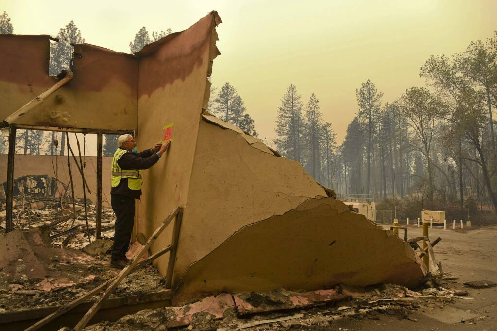 An official with the Office of Statewide Health Planning & Development marks a building damaged by wildfire, in Paradise, Calif., Monday, Nov. 12, 2018. (Hector Amezcua/The Sacramento Bee via AP)