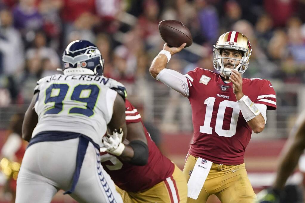 San Francisco 49ers quarterback Jimmy Garoppolo passes against Seattle Seahawks defensive tackle Quinton Jefferson during the second half in Santa Clara, Monday, Nov. 11, 2019. (AP Photo/Tony Avelar)