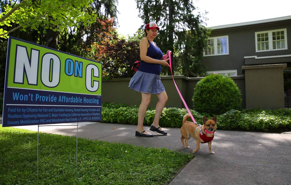 A supporter of Measure C, who did not want her name used, walks past a sign opposed to Measure C along McDonald Avenue, in Santa Rosa on Friday, May 5, 2017. (Christopher Chung/ The Press Democrat)