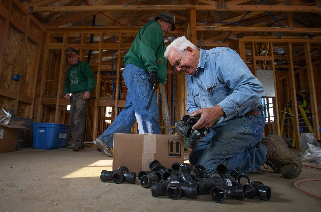 Dick Crawford of Livermore looks for the correct pipe fitting in a home destroyed by the Valley Fire in Middletown. Volunteers with the Hope Crisis Response Network are rebuilding homes destroyed in the Valley Fire and will continue their efforts in Santa Rosa after the Tubbs Fire. (photo by John Burgess/The Press Democrat)