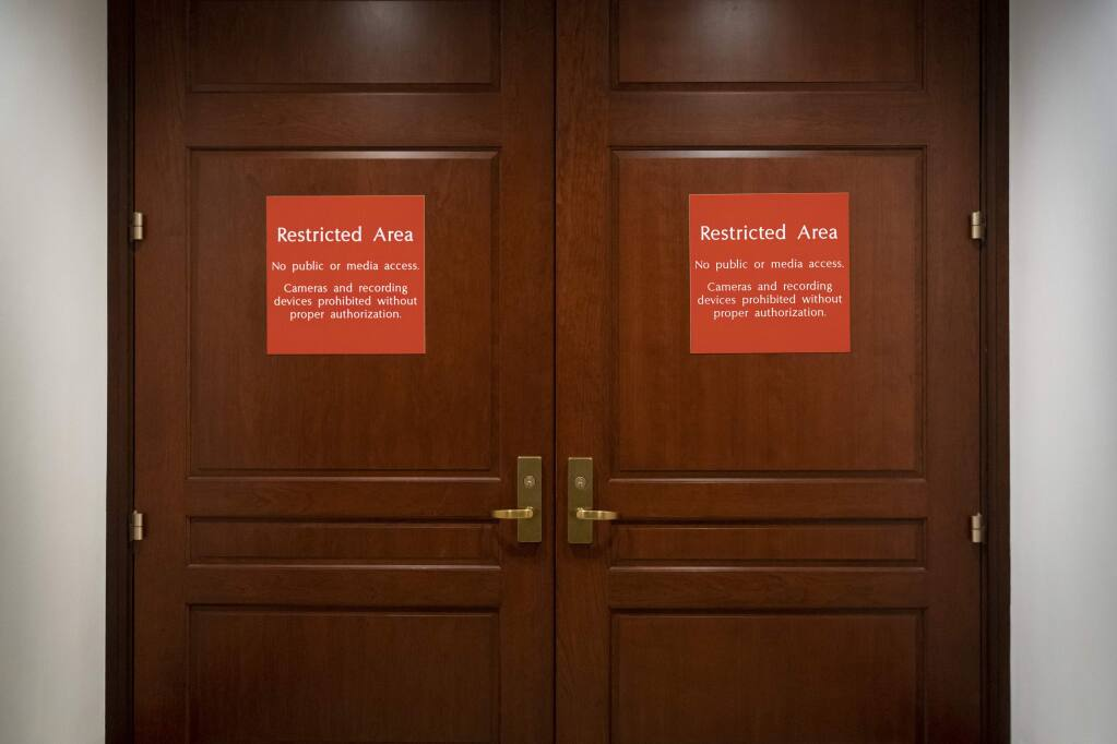 In this Nov. 6, 2019, photo, bright red signs alert non-authorized personnel at the entrance to the House SCIF, the Sensitive Compartmented Information Facility, located three levels beneath the Capitol where witnesses and lawmakers hold closed interviews in the impeachment inquiry on President Donald Trump's efforts to press Ukraine to investigate his political rivals, in Washington. (AP Photo/J. Scott Applewhite)