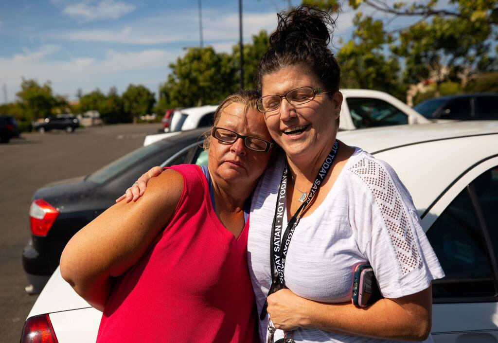 COTS homeless outreach specialist Cecily Kagy, right, embraces Emily Morris-Jarboe after visiting with Morris-Jarboe and other homeless people in front of the Target store in Rohnert Park, California, on Thursday, August 8, 2019. (Alvin Jornada / The Press Democrat)