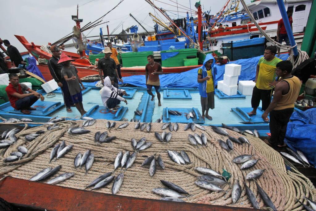 Fish vendors wait for customers at a fishing port in Banda Aceh, Aceh province, Indonesia in 2014. (AP Photo/Binsar Bakkara)