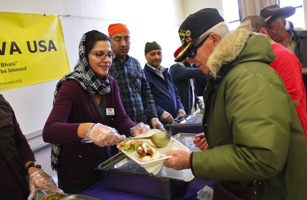 Rupinder Kaur Malhi, left, of Sikh Seva USA, serves lentil soup to veteran Stanley Fife at the Veterans Memorial Building in Santa Rosa on Tuesday, December 19, 2017. (Christopher Chung/ The Press Democrat)