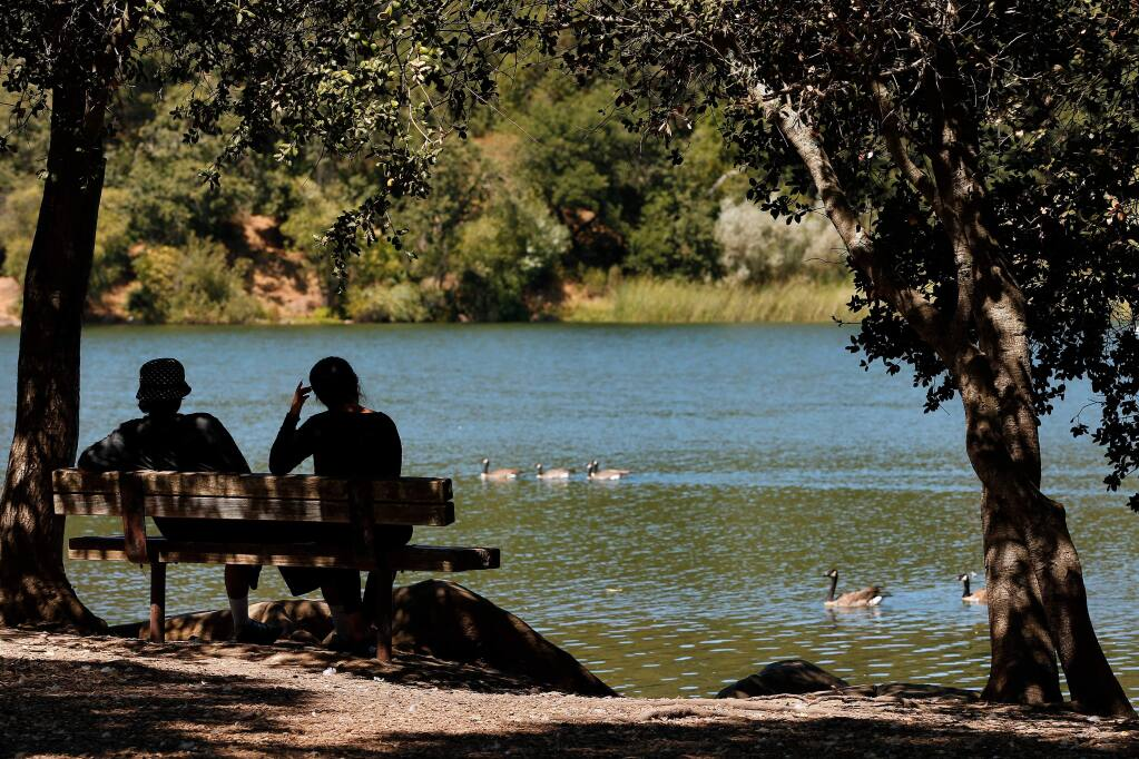 A couple stays cool in the shade while they chat beside Lake Ralphine in Santa Rosa, California, on Wednesday, August 14, 2019. (Alvin Jornada / The Press Democrat)