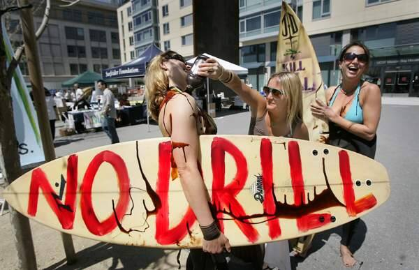 Adrienne Moore of San Francisco uses chocolate syrup in place of oil to prove a point on surfers Kathleen Egan, left and Emilia Lipcsei, during a protest rally, Thursday April 16, 2009 outside of a hearing on offshore energy development, at the UC San Francisco Mission Bay Campus.(Kent Porter / The Press Democrat)2009