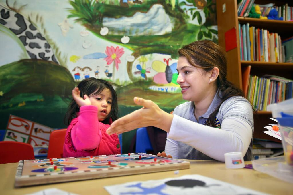 Childcare provider Enedina Reyes gets a high-five from two-year-old Sarahy Argota after completing a puzzle at La Luz, in Sonoma on Tuesday, January 20, 2015. (Christopher Chung/ The Press Democrat)