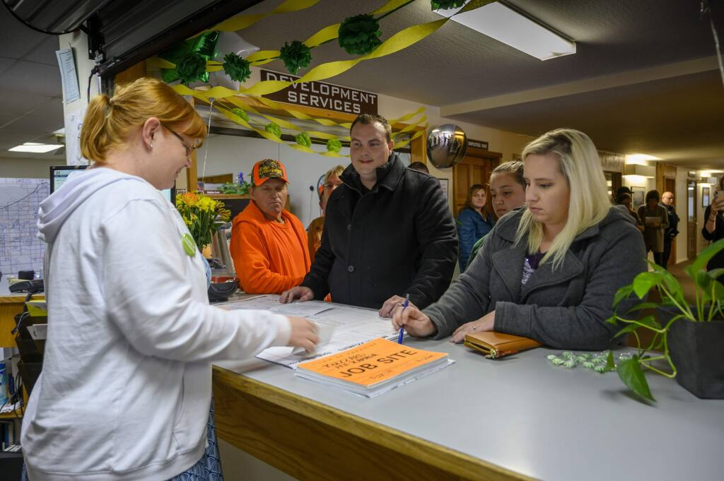 In this photo taken Thursday, March 28, 2019, Anne Vierra,with the town of Paradise, takes payment for the first building permit since the Camp Fire as Jason and Meagann Buzzard plan to rebuild their home in Paradise, Calif. Small signs of rebuilding a Northern California town destroyed by wildfire are sprouting this spring, including the issuing of the first permit to rebuild one of the 11,000 homes destroyed in Paradise five months ago. A city hall clerk on Thursday issued the couple a building permit to replace their home destroyed by the Nov. 8 fire that killed 85 people. The couple told reporters they never thought about leaving. Paradise Mayor Jody Jones said the Buzzards' permit is a sign that the town will rebuild.(Hector Amezcua/The Sacramento Bee via AP)