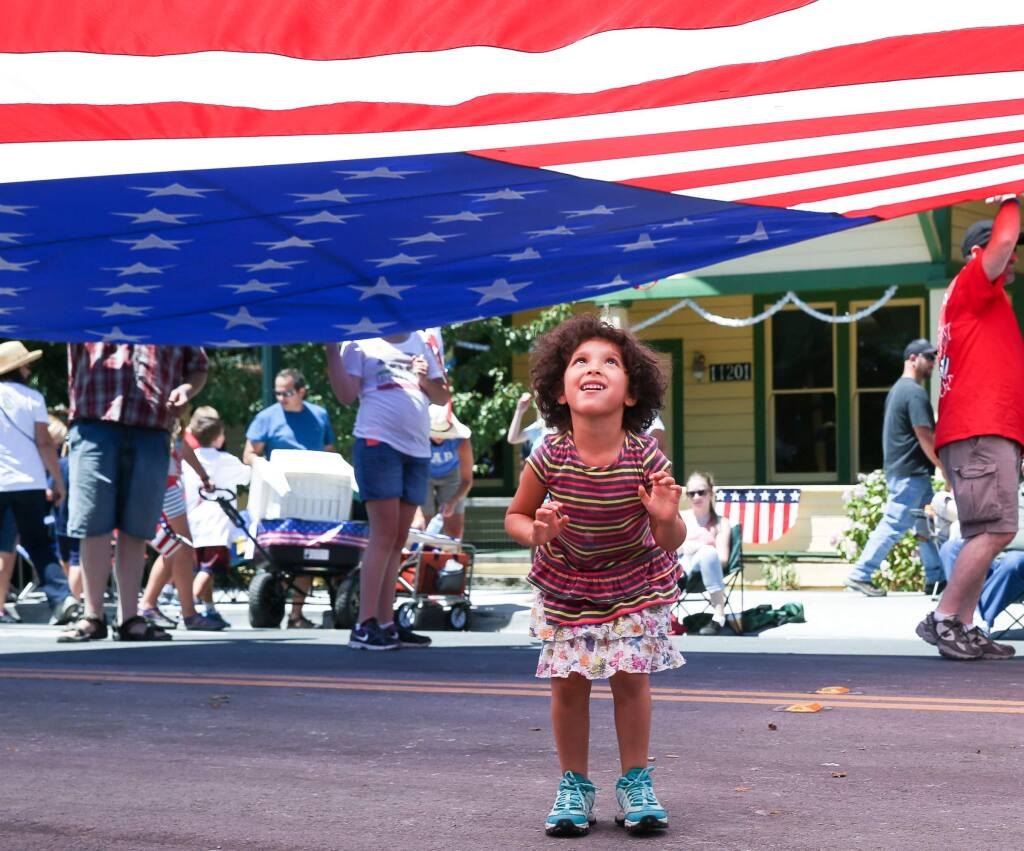 Emma Guevara, 4, of Rohnert Park plays under the flag at the end of the 39th annual Penngrove Parade on Sunday, July 6, 2014.