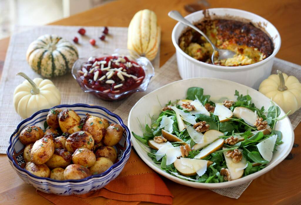 Papas a la diabla, cranberry sauce with raisins and slivered almonds, corn pudding, and salad with pears, cheese and walnuts. Photo taken in Santa Rosa on Wednesday, Nov. 20, 2019. (BETH SCHLANKER/ The Press Democrat)