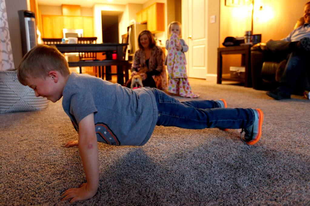 Cody Nix, 6, practices his pushups while his family unwinds at the end of the day in their new home in Santa Rosa, California, on Wednesday, March 21, 2018. The Nix Family experienced an insurance shortfall when they tried to rebuild their home in the Larkfield neighborhood burned down in the Tubbs fire. (Alvin Jornada / The Press Democrat)