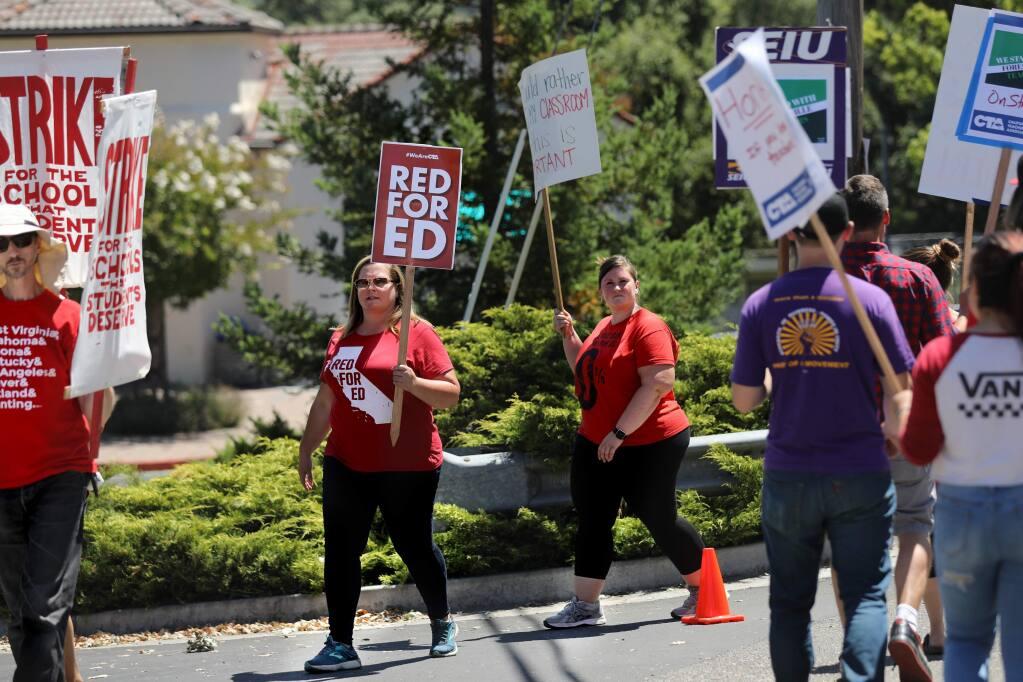 Teachers Kim Andrews, center left, and Marni Self, center right, strike with members of the Forestville Teacher's Association in front of Forestville School in Forestville on Monday, Aug. 12, 2019. (BETH SCHLANKER/ The Press Democrat)