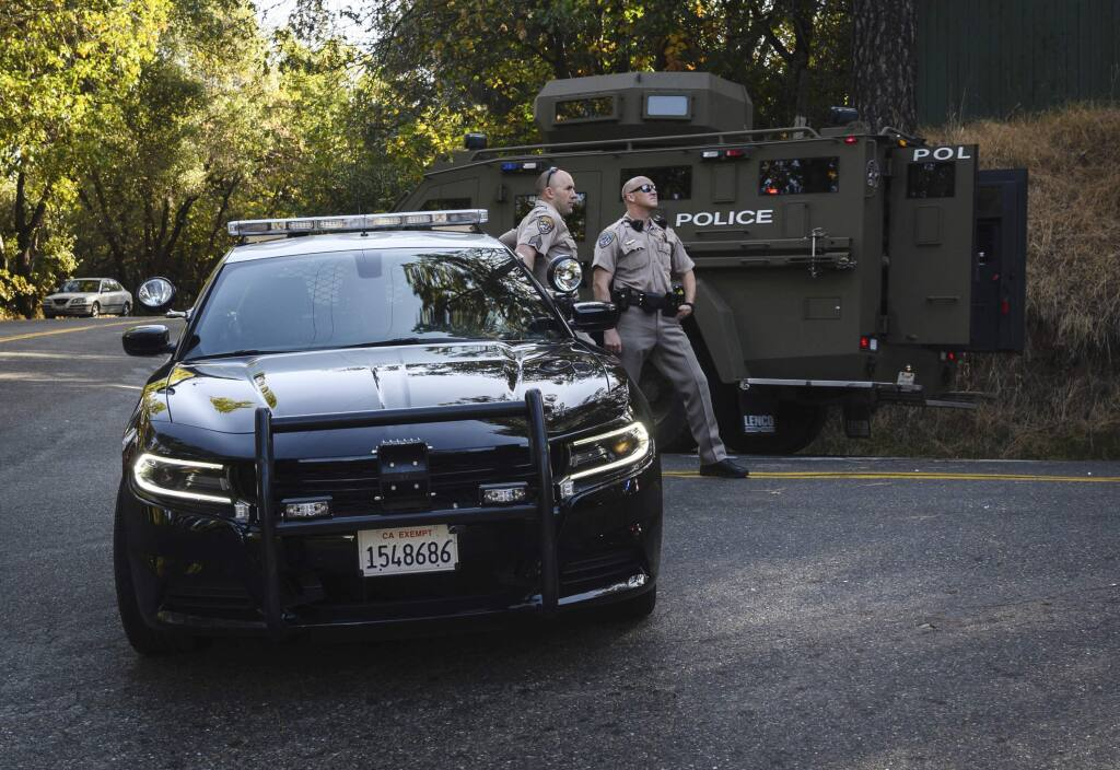 California Highway Patrol officers block off a road where El Dorado County sheriff's deputy Brian Ishmael was killed responding to an early morning call, as an armored vehicle passes by in Somerset, Calif., Wednesday, Oct. 23, 2019. Ishmael was shot to death Wednesday while responding to a call in the rural Sierra Nevada foothills, officials said. The El Dorado County Sheriff's Office said Deputy Brian Ishmael was fatally shot in the community of Somerset and that a ride-along passenger with him was also shot and injured. (Daniel Kim/The Sacramento Bee via AP)