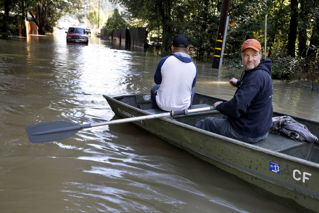 Bruce MacDonell uses his boat to rescue motorist Renaldo Carrasco after his car became stuck in flood waters on Neeley Rd on Friday, February 10, 2017 in Guerneville, California . (BETH SCHLANKER/The Press Democrat)