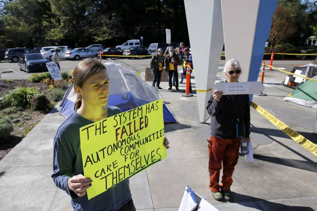 Adrien Shader and Annette Pierson hold signs in support of members of the homeless community outside the Board of Supervisors Chambers on Tuesday, April 17, 2018 in Santa Rosa, California . (BETH SCHLANKER/The Press Democrat)