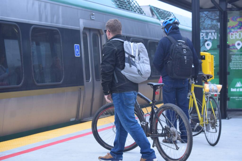 Bob Hostutler, left, and another cyclist wheel their bikes toward the 8:31 a.m. train at Santa Rosa's downtown station on Jan. 23, 2018. (James Dunn / North Bay Business Journal)