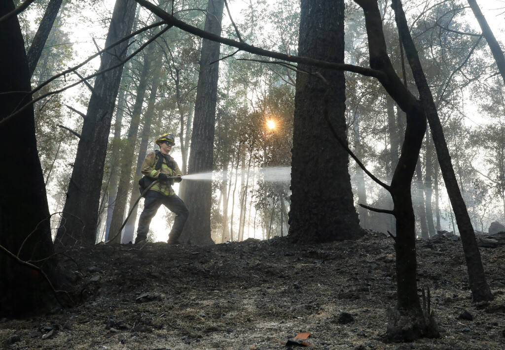 Lathrop Manteca Fire Department firefighter John Legasa puts out hot spots on a hillside at Rombauer Vineyards in St. Helena on Tuesday, Sept. 29, 2020.  (Christopher Chung/ The Press Democrat)