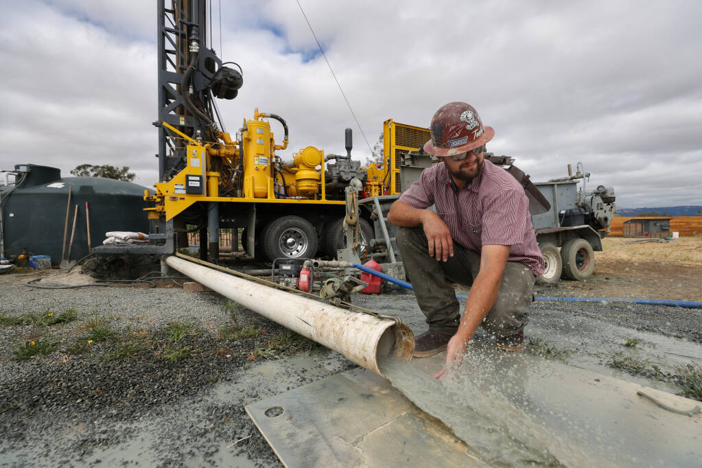 Weeks Drilling & Pump Co. operator foreman Nick Riojas checks water flowing from a new well on a vineyard property near Sonoma on Tuesday, June 22, 2021.  (Christopher Chung / The Press Democrat)