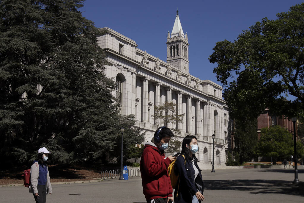 FILE - In this March 11, 2020, file photo, people wear masks while walking past Wheeler Hall on the University of California campus in Berkeley, Calif. (AP Photo/Jeff Chiu, File)