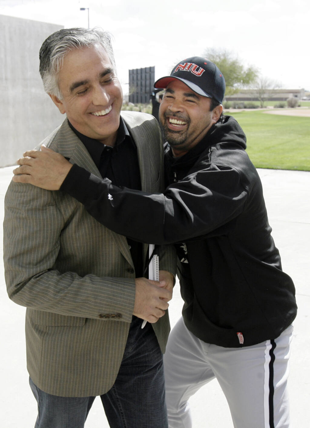 Then-Chicago White Sox manager Ozzie Guillen jokes with ESPN's Pedro Gomez, left,  after a news conference during spring training on Saturday, Feb. 16, 2008, in Tucson, Arizona. (M. Spencer Green / ASSOCIATED PRESS)