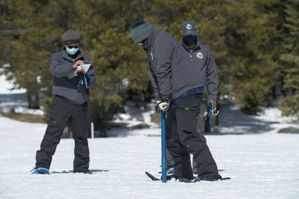 Assisted by Ramesh Gautam, left and Anthony Burdock right, Sean de Guzman, chief of snow surveys for the California Department of Water Resources, checks the depth of the snowpack during the second snow survey of the season at Phillips Station near Echo Summit, Calif., Tuesday, March 2, 2021. The survey found the snowpack at 56 inches deep with a water content of 21 inches. (AP Photo/Randall Benton)