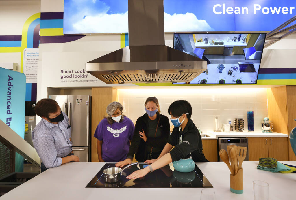 Sonoma Clean Power Advanced Energy Center staff member James Quan, right, demonstrates how an induction cooktop works to teachers Julia Varboncoeur and Marcella Barrios, and Logan Pitts, senior field representative for Senator Bill Dodd, in Santa Rosa on Wednesday, July 21, 2021.  (Christopher Chung/ The Press Democrat)