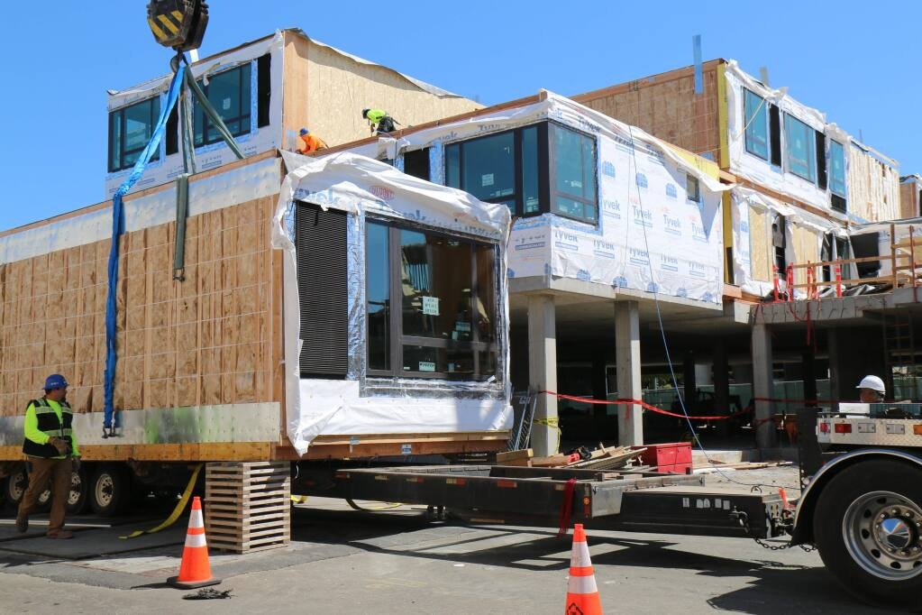 As seen from Davis Street, two-room modules for the AC Hotel project are hoisted into position on Tuesday, June 18, 2019. (Jeff Quackenbush / North Bay Business Journal)