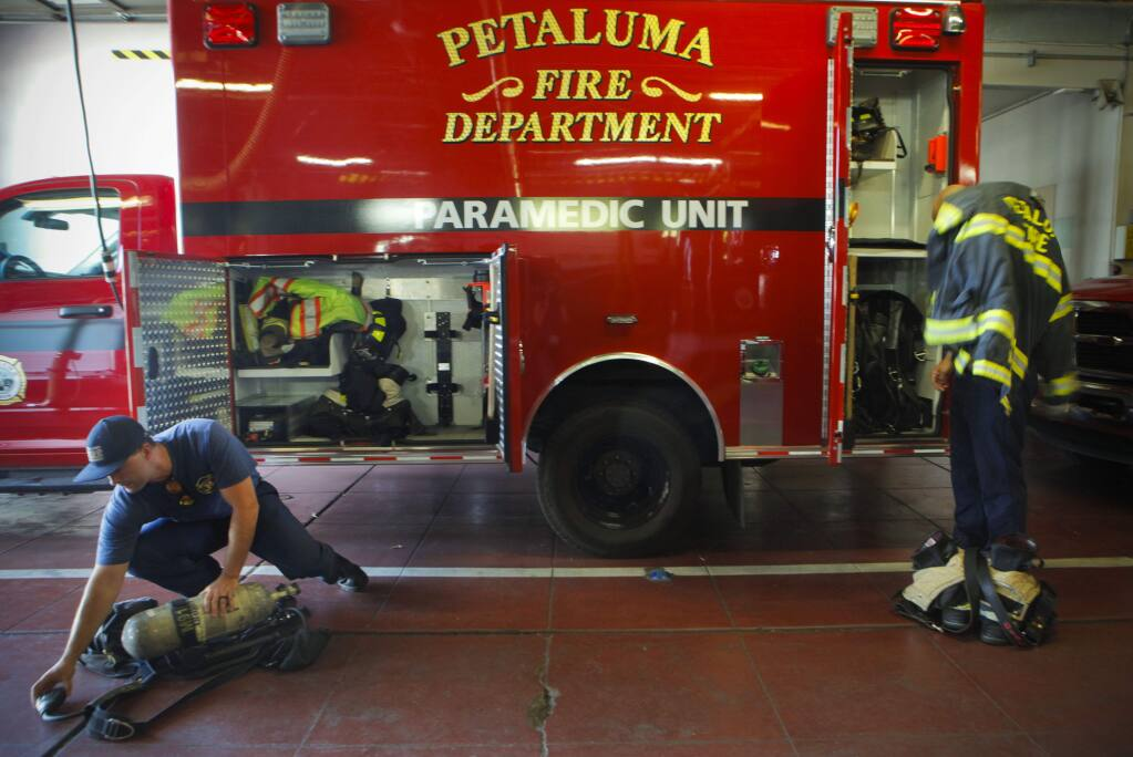 Firefighter/Paramedic Jamin Perkins (left) and firefighter Matt Dealba checkout the rigs at Station One in downtown Petaluma at the beginning of their shift. (CRISTINA PASCUAL/ARGUS-COURIER STAFF)