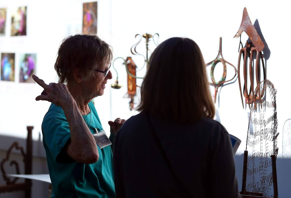 Artist Susandra Spicer, left, talks with Shay Reeves, of Colorado, about her metal art sculptures, during the Sonoma County Art Trails Open Studio Tour, in Sebastopol on Sunday, October 12, 2014. (Christopher Chung/ The Press Democrat)