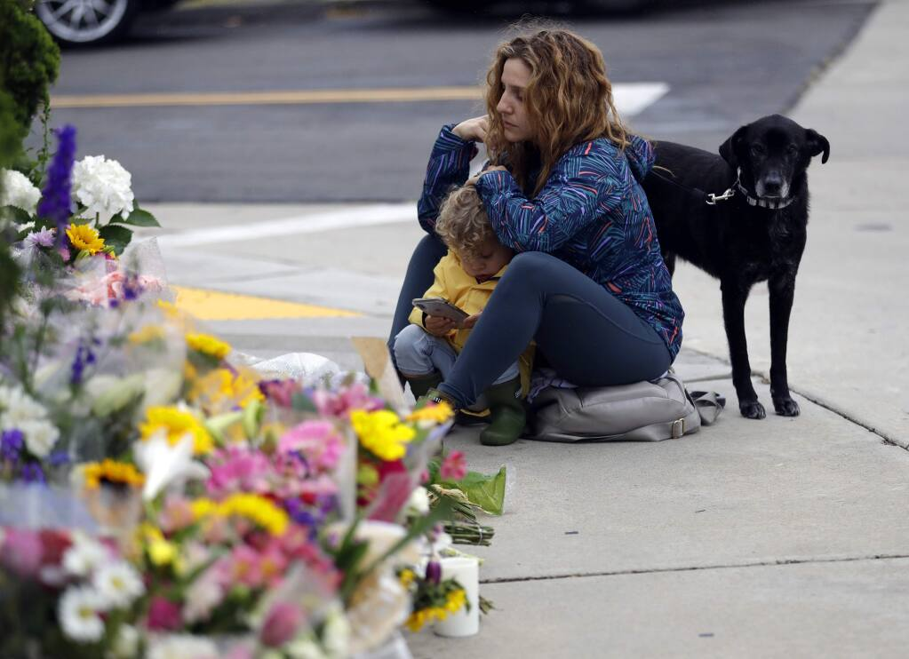 Ali De Leon pauses at a growing memorial with her son Leo and her dog Vinny across the street from the Chabad of Poway synagogue in Poway, Calif., on Monday, April 29, 2019. A gunman opened fire on Saturday, April 27 at the synagogue as dozens of people were worshipping exactly six months after a mass shooting in a Pittsburgh synagogue. (AP Photo/Greg Bull)