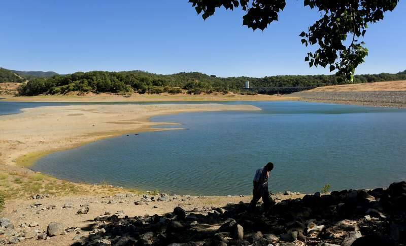 (FILE PHOTO) Familiar drought landmarks begin to reappear on Lake Mendocino in Ukiah, as Travis Parsons of Ukiah finishes a walk around the shoreline, Wednesday June 18, 2014. (Kent Porter / Press Democrat) 2014