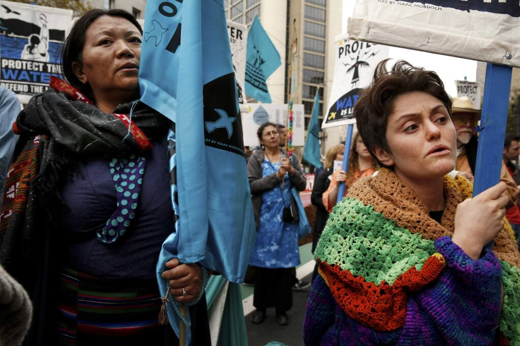 Tsering Yangkey, left, of Tibet, and Tanya Fromberg, of London, protest the Dakota Access oil pipeline along Market Street Tuesday, Nov. 15, 2016, in San Francisco, Calif. The protest brought thousands of demonstrators to the streets of San Francisco on Tuesday. Before sunrise, protesters formed a circle in a downtown plaza and burned sage before walking down Market Street. (Santiago Mejia/San Francisco Chronicle via AP)
