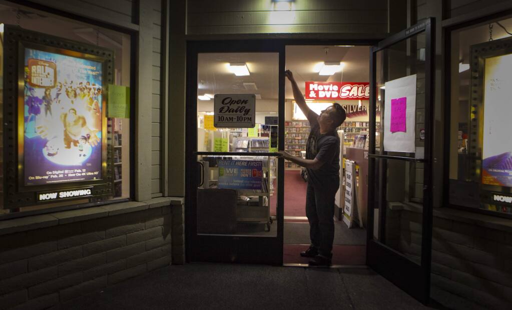 Petaluma, CA, USA._Monday, July 22, 2019._Rigoberto Jaime, the manager of Silver Screen Video closes the doors for the night. The movie rental store will be closing on August 25, 2019, marking the end of an era. (CRISSY PASCUAL/ARGUS-COURIER STAFF)