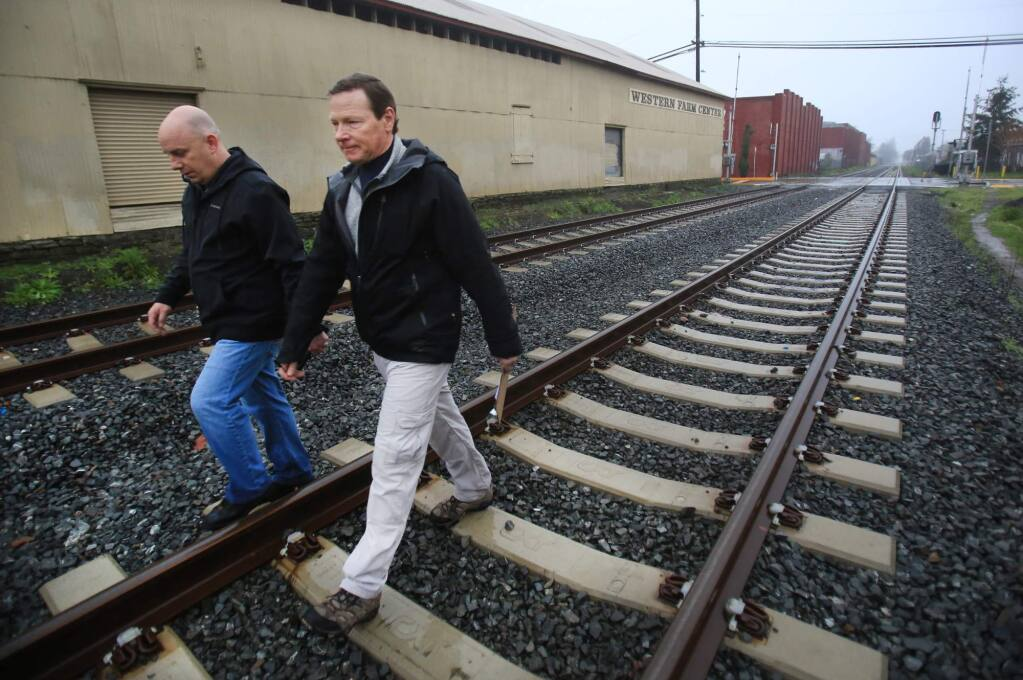 Santa Rosa police Capt. John Cregan, left, and Santa Rosa Mayor Tom Schwedhelm walk the SMART tracks as the two participate in a past homeless census survey, in Santa Rosa. (Kent Porter / Press Democrat, 2016)