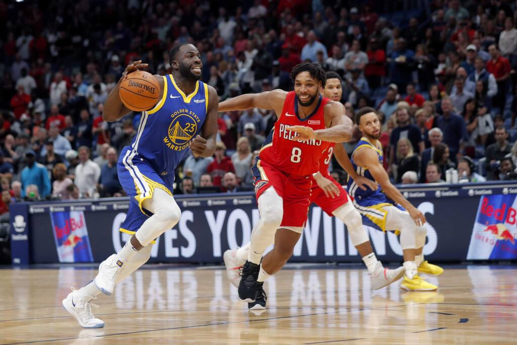 Golden State Warriors forward Draymond Green (23) drives to the basket against New Orleans Pelicans center Jahlil Okafor (8) in the first half of an NBA basketball game in New Orleans, Monday, Oct. 28, 2019. (AP Photo/Gerald Herbert)