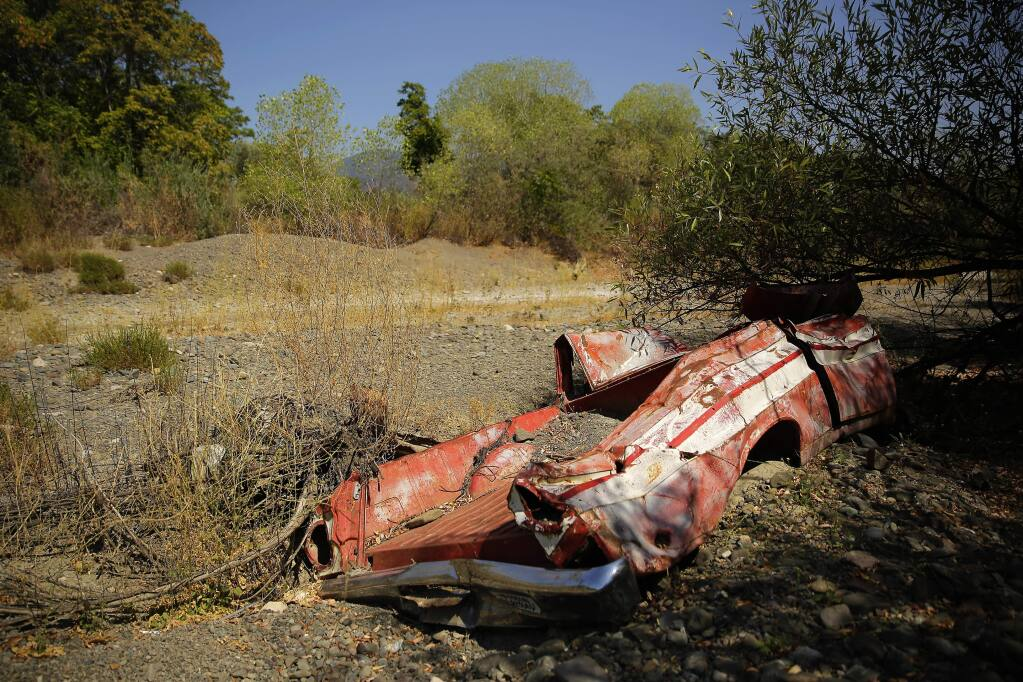 An old truck embedded in the Kelsey Creek bed lays completely dried near downtown Kelseyville on Saturday, August 9, 2014. (Conner Jay/The Press Democrat)