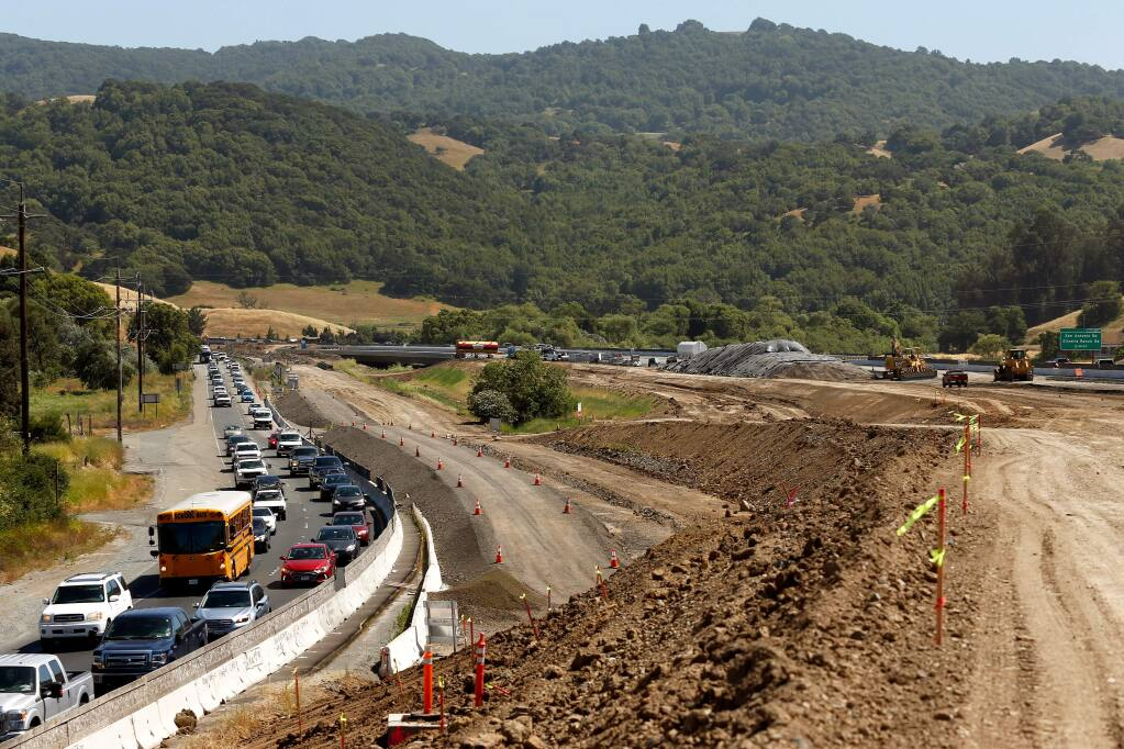 Motorists drive northbound in afternoon traffic on Highway 101, beside the road construction zone south of Petaluma, on Wednesday, May 30, 2018. The new bridge over San Antonio Creek is seen at center, in the background. (Alvin Jornada / The Press Democrat)