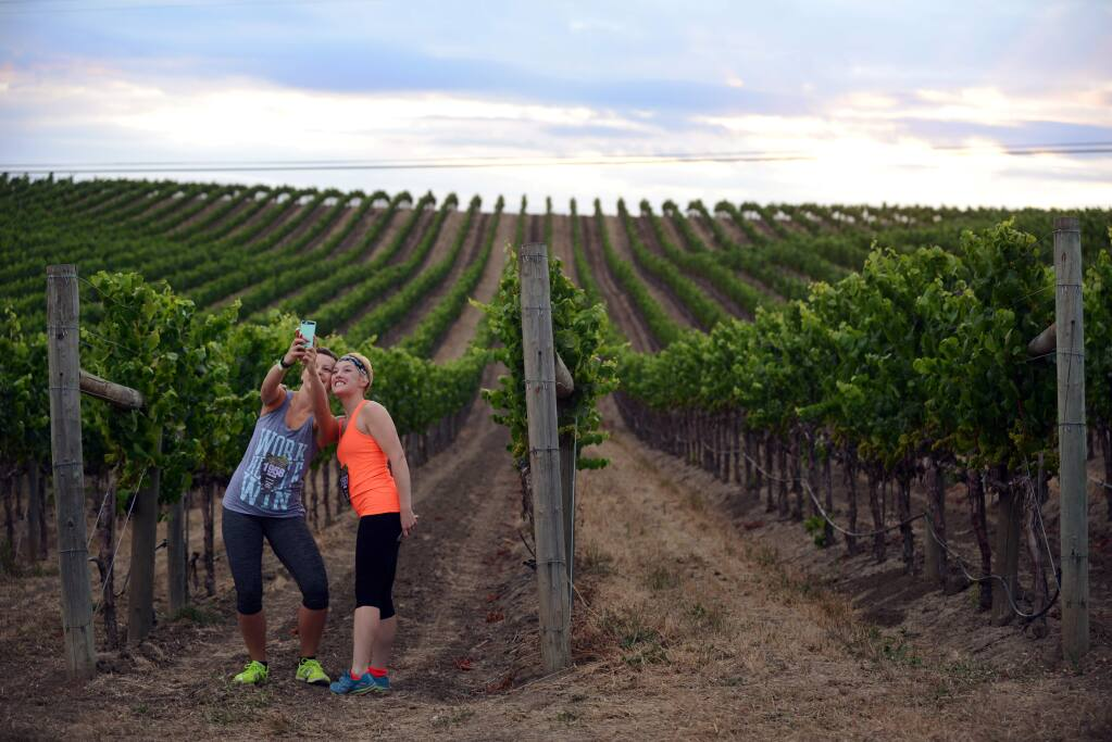 Marisa Spencer, left, from Pittsburgh, Pennsylvania and Madlyn Oltman of Charleston, West Virginia, taking selfies near a vineyard at Cuvaison Estate Wines in Napa before the start of the Napa-to-Sonoma Wine Country Half Marathon held on July 19, 2015. (Photo: Erik Castro/for The Press Democrat)