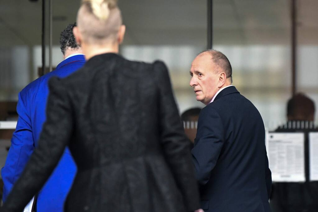 Plaintiff, British cave expert Vernon Unsworth, right, arrives at U.S. District Court Wednesday, Dec. 4, 2019, in Los Angeles. Tesla CEO Elon Musk is going on trial for his troublesome tweets in a case pitting the billionaire against the British diver he allegedly dubbed a pedophile. (AP Photo/Mark J. Terrill)