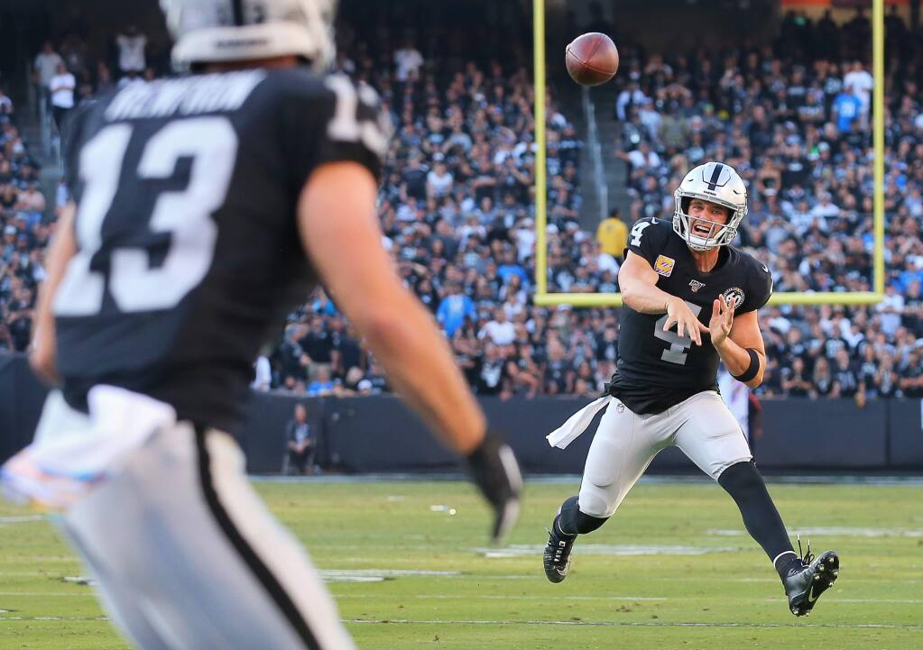 Oakland Raiders quarterback Derek Carr delivers a touchdown pass to wide receiver Hunter Renfrow against the Detroit Lions in Oakland on Sunday, Nov. 3, 2019. (Christopher Chung / The Press Democrat)
