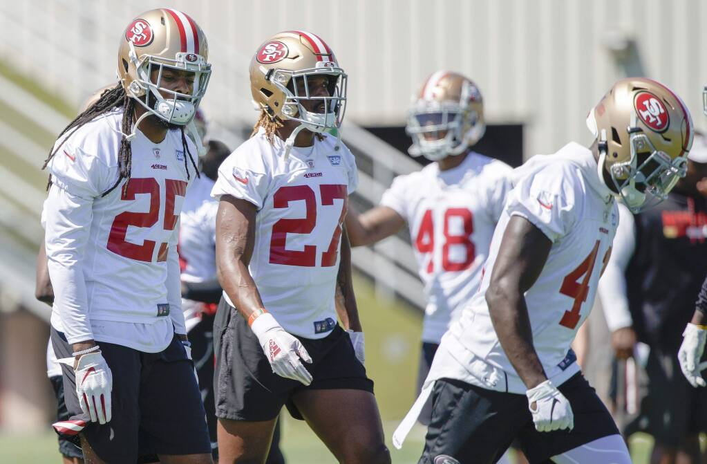 The San Francisco 49ers' Richard Sherman, left, Adrian Colbert and Emmanuel Moseley, right, warm up during practice at the team's training facility in Santa Clara, Tuesday, June 11, 2019. (AP Photo/Tony Avelar)