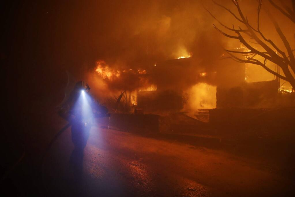 A firefighters gets in position to hose down flames as a home burns in the Getty fire area along Tigertail Road, Oct. 28, 2019, in Los Angeles. (AP Photo/Marcio Jose Sanchez)