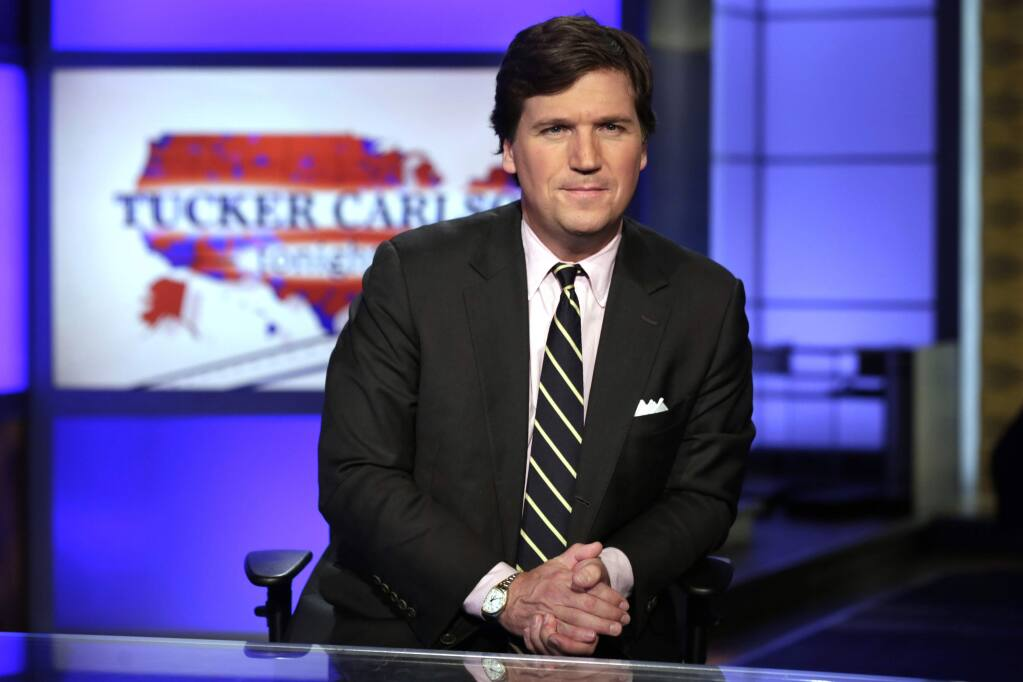 FILE - In this March 2, 2017 file photo, Tucker Carlson, host of 'Tucker Carlson Tonight,' poses for photos in a Fox News Channel studio, in New York. Carlson says he felt a moral obligation to meet with President Donald Trump to warn him about the seriousness of coronavirus. He told Vanity Fair that while he didn't feel it was his role, his wife convinced him to request the meeting, which took place on March 7. (AP Photo/Richard Drew, File)