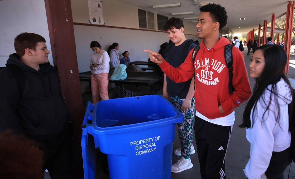 From left, Piner High School teammates Donovan Carrillo, Noah Hatfield and Yonaton Isack greet one another during lunch break, Thursday, Nov. 21, 2019, at right is Lezkena Nhock. Football players are part of a recycling program at the school, and help students sort out trash and recycling. (Kent Porter / The Press Democrat)