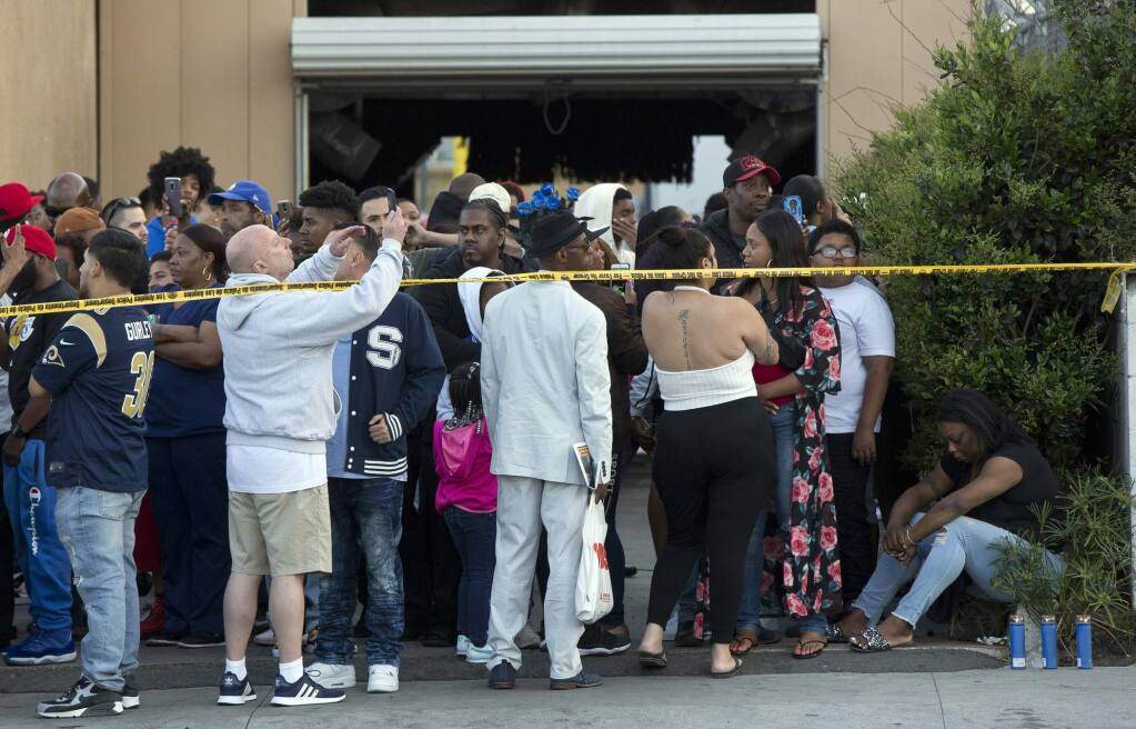 People gather near the Marathon Clothing store of rapper Nipsey Hussle in Los Angeles, Sunday, March 31, 2019. (AP Photo/Damian Dovarganes)