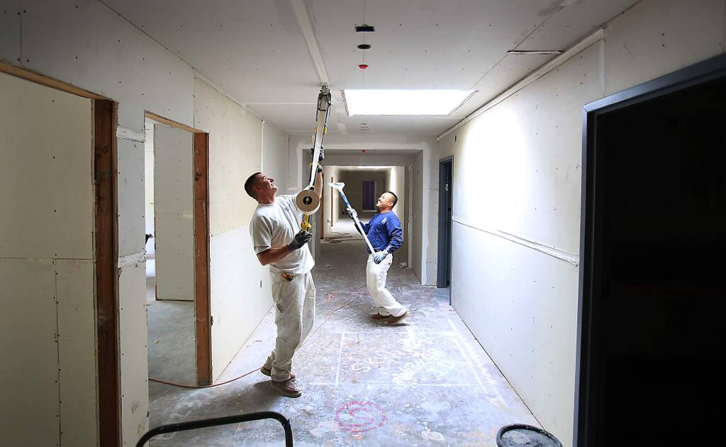 Brad Pedersen, left and Victor Casanas tape and seal wallboard at the SAY Dream Center Friday Aug. 28, 2015 in Santa Rosa.. (Kent Porter / Press Democrat) 2015