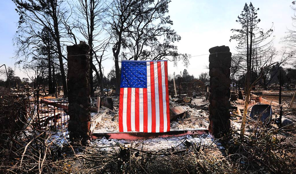 A homeowner displays an American flag amidst the Tubbs fire destruction on Willowview Court in Santa Rosa on Thursday Oct. 12, 2017. (Kent Porter/The Press Democrat)
