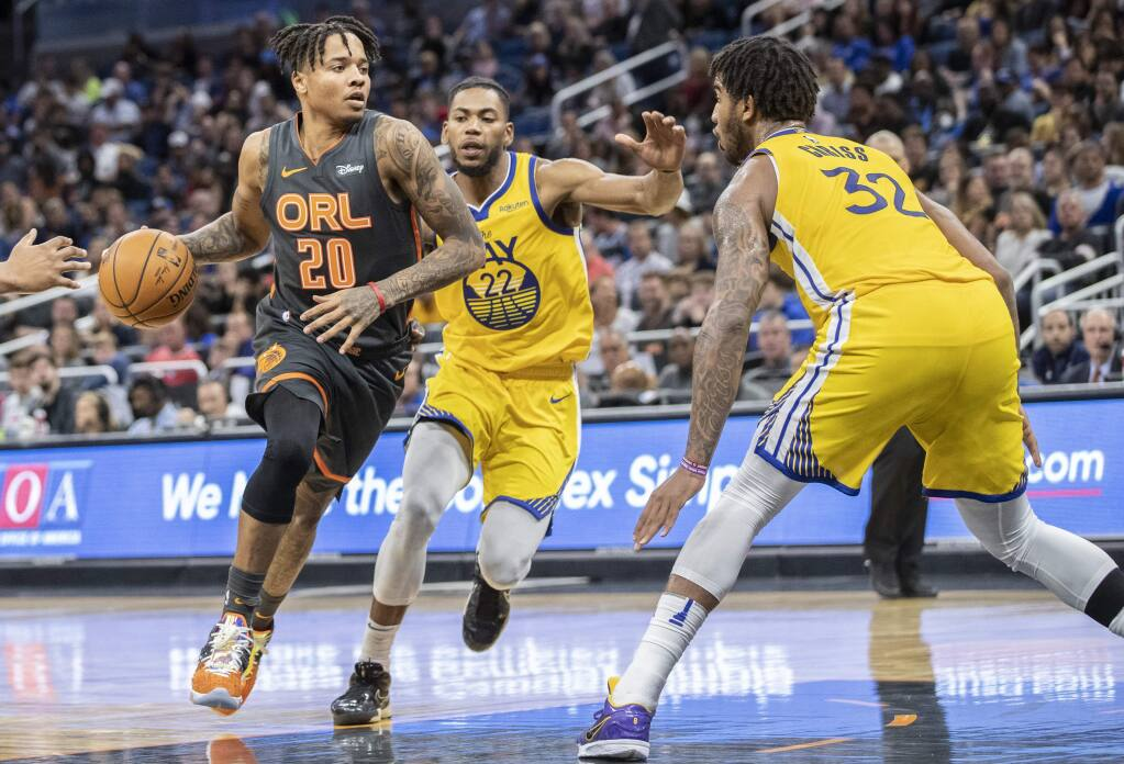 Orlando Magic guard Markelle Fultz (20) dribbles toward the basket on Golden State Warriors forward Glenn Robinson III (22) and forward Marquese Chriss (32) during the first half of an NBA basketball game, Sunday, Dec. 1, 2019, in Orlando, Fla. (AP Photo/Willie J. Allen Jr.)